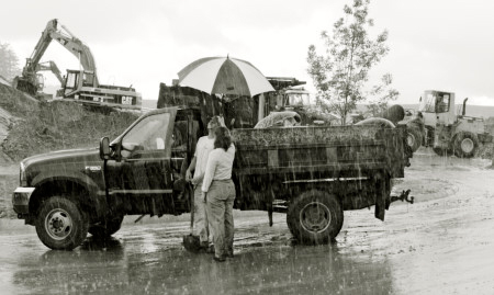 couple next to dump truck in the rain