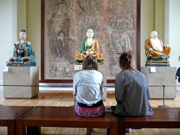 Sitting With by Dorothee Lang -- museum-goers sitting in front of Buddha statues